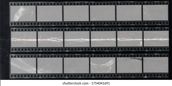 long 35mm filmstrips behind protection foil with deep scratches, cool photo placeholder.
