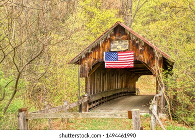 A long abandoned covered bridge still stands with its weathered wood