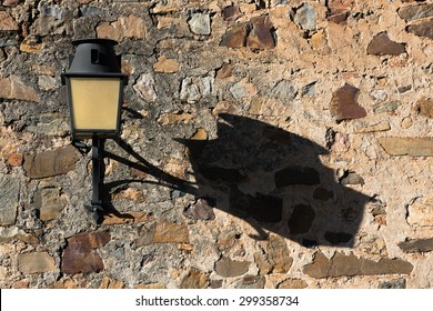 The long afternoon shadow of a lamp post of a street light against an old castle wall in Spain
