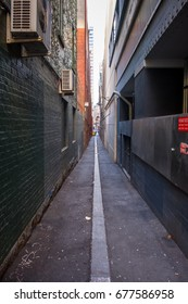 Long alley way with no people. Green wall.