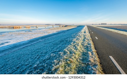 Long asphalt country road with white stripes on the top of a dike in the winter season. The photo was taken early on a sunny morning in the Noordwaard polder, Biesbosch, North Brabant.