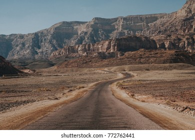 Long asphalt road and rocky hill on desert in Israel. Timna National Park.