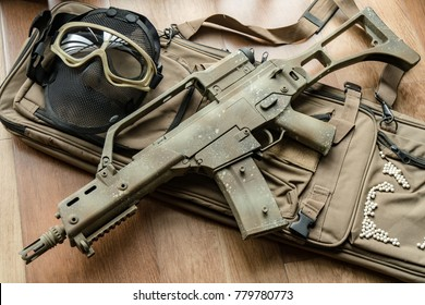 Long automatic airsoft gun Plastic body Put on a gun pocket. The side is a black bulletproof mask and brown bulletproof glasses laid on a wooden floor.