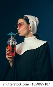 Long awaited lounge chilling. Medieval young woman as a nun in vintage clothing sitting on the chair on dark blue background. Drinking lemonad or coctail. Concept of comparison of eras.