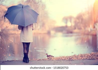 long background girl umbrella / horizontal view rainy autumn day young woman with umbrella