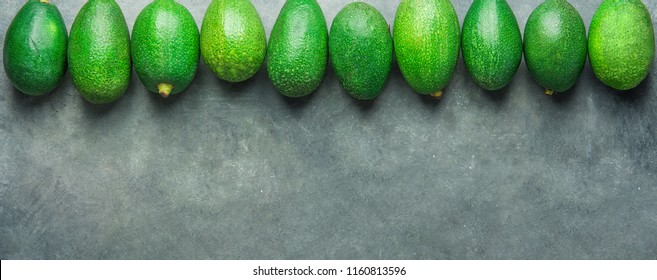 Long Banner Header. Bunch of Ripe Raw Avocados Arranged in Upper Border on Dark Stone Background. Top View Copy Space. Healthy Lifestyle Vitamins Oil. Mediterranean Cuisine Concept. Poster Template