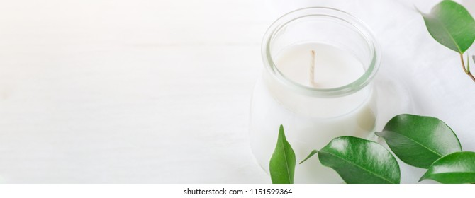 Long Banner for Organic Cosmetics Wellness White Candle in Glass Jar Fresh Tree Branches with Green Leaves on Wood Background. Spa Body Care Meditation Purity Concept. Minimalist Style. Copy Space