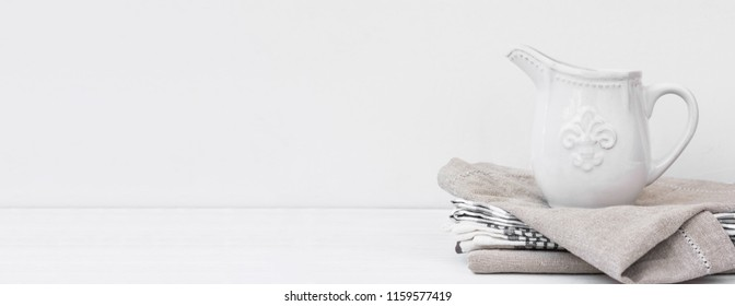 Long banner white vintage pitcher on stack of linen cotton towels. Kitchen interior home textile. Store header culinary site template. Minimalist scandinavian style. Copy space