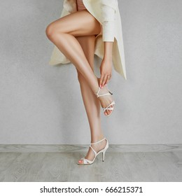 Long bare woman legs in high heel beige sandals. Close up of fastening shoes.