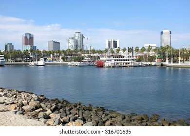 LONG BEACH, CA - FEBRUARY 21, 2015: Rainbow Harbor and city skyline. The harbor cruise boat Grand Romance  river boat at dock in Rainbow Harbor with city skyline in background.