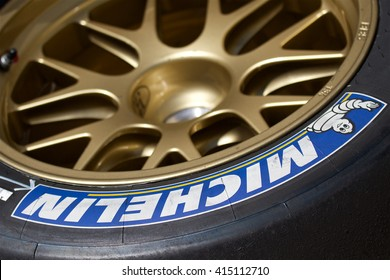 LONG BEACH, CA - MAY 1, 2016: A single Michelin racing tire and gold wheel sit stacked in a racing facility. Michelin is one of the three largest tire manufacturers in the world.