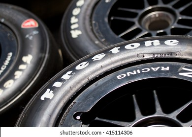 LONG BEACH, CA - MAY 1, 2016: Three used Firestone racing tires and wheels sit stacked in a racing facility. Firestone is a subsidiary of the Bridgestone tire company.
