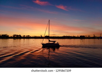 Long Beach, CA / USA - January 26, 2019: A silhouette of a sailboat during sunset in the Long Beach Harbor