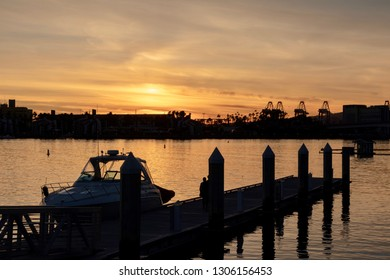 Long Beach, CA / USA - January 26, 2019: A boat by a pier in the Long Beach Harbor during sunset