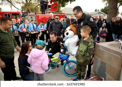 Long Beach, California Dec. 21, 2019. Fire Chief Xavier Espino (kneeling) and Police Chief Robert Luna deliver Christmas presents to the Navarro - Sexton family as part of an annual tradition.