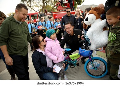 Long Beach, California Dec. 21, 2019. Long Beach Fire Chief Xavier Espino delivers  Christmas presents to the Navarro - Sexton family as part of an annual holiday tradition.