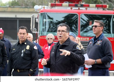 Long Beach, California Dec. 21, 2019. Police chief Robert Luna addresses volunteers as fire chief Xavier Espino (left) looks on before Long Beach's annual holiday toy caravan sets off.
