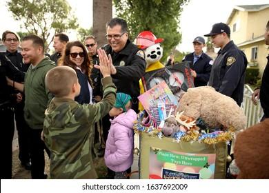 Long Beach, California Dec. 21, 2019. Hugo Navarro, 9, gives a high five to Long Beach Police Chief Robert Luna as his family receives Christmas presents.
