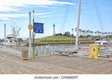 LONG BEACH, CALIFORNIA - JAN 30, 2019: Sign welcoming visitors to Rainbow Harbor with boats and lighthouse in the background.