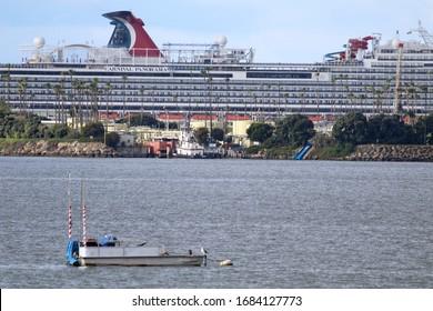 Long Beach, California;  March 25, 2020. The coronavirus causes the Carnival Cruise Ship, Panorama, to sit idle beyond an oil island in Long Beach, California.