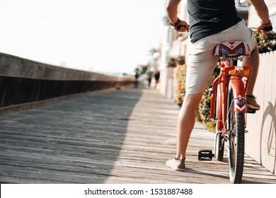 LONG BEACH, CALIFORNIA - OCTOBER 14, 2019 - A man rides a bicycle along a beach on boardwalk.