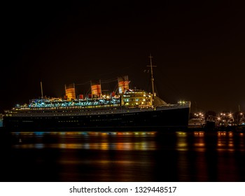 Long Beach, California / United States – April 29, 2016: The RMS Queen Mary docked with its lights of for the eveing.