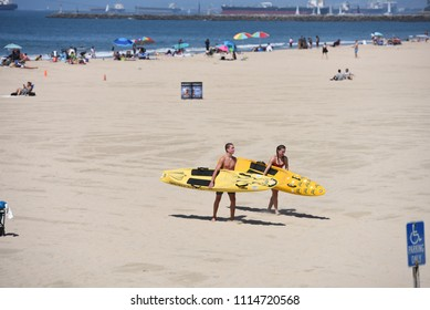 Long Beach, California, USA - June 10, 2018: Unidentified surfers with their boards on their way to the beach. June 12, 2017, Long Beach, CA.
