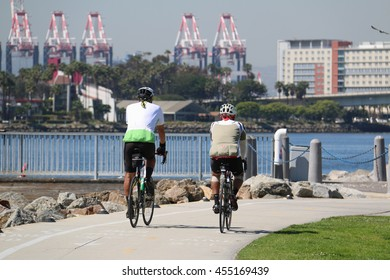 Long Beach, California, USA - March 16, 2016: Cyclists are riding bicycles on a small street along coastline of Long Beach, California.