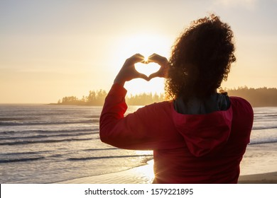 Long Beach, Near Tofino and Ucluelet in Vancouver Island, BC, Canada. Adventurous Girl making Hearth Shape with Hands with golden sunset on the Pacific Ocean Coast in the background.