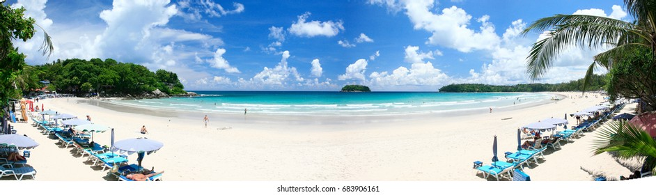 The long beach on the island is popular with tourists. The beach has white sand, blue sea, blue sky, white clouds, beach chairs. Beach umbrellas and nature complete. Panorama view at phuket, thailand