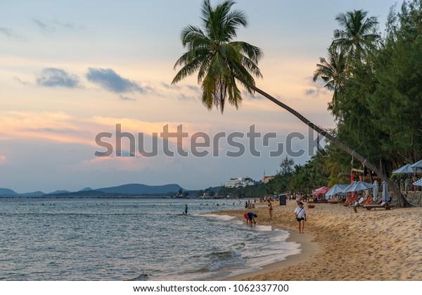 LONG BEACH, PHU QUOC ISLAND, VIETNAM - NOVEMBER 17,  2017: Beach coastline at sunset time. People walk and relax on beach.