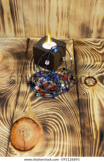 Long beads of multi-colored glass beads and a candle in a wooden candlestick on a wooden background.