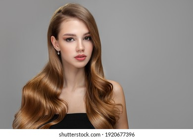 Long beautiful wavy hair. Portrait of a woman with shiny blond hair. copycpase