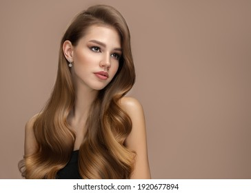 Long beautiful wavy hair. Portrait of a woman on a brown background with shiny hair. copycpase