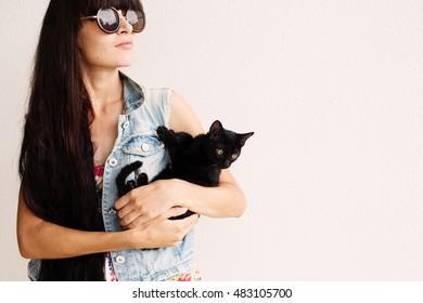 Long black hair fashion girl in sunglasses holding little black cat on white wall background