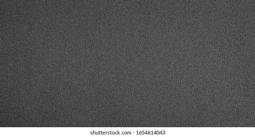 Long black metallic textured plate close up. Texture and background