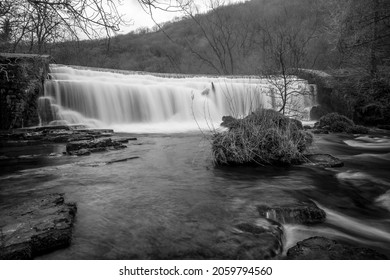 Long black and white exposure of the Monsal Dale Weir waterfall and River Wye on the Monsal Trail in the Peak District - Shutterstock ID 2059794560