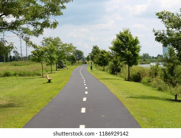 The long blacktop pathway in the park on a sunny hot summer day.