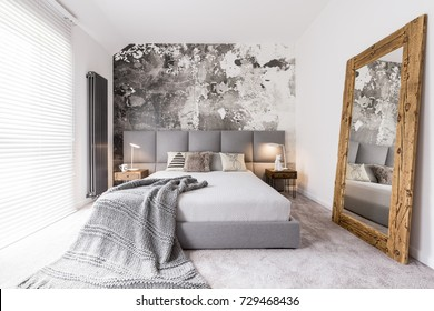 Long blanket lying on a double bed in a rectangular, monochromatic bedroom with a radiator next to a window with blinds