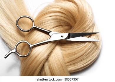 long blond human hair close-up and scissors