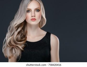 Long blonde hair model woman over black background film effect. Beauty concept. Studio shot.