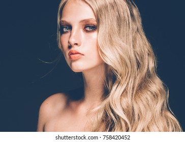 Long blonde hair model woman over black background film effect. Beauty concept. Studio shot.