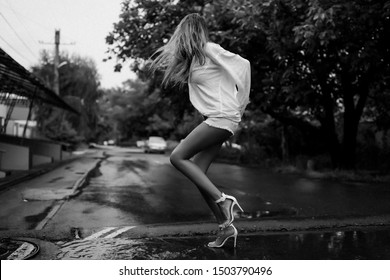 Long blonde hair shaking and wet after the summer pouring rain. Lady having fun outdoor on the street in her man's shirt and on high heel shoes with open toes. Puddles and road with water streams.