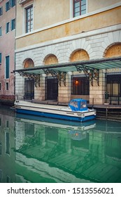 Long blue boat in front of a building in the channels of venice, italy