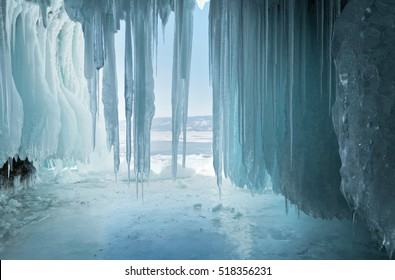 Long  blue icicles in the ice cave at coastal cliffs. Unusual natural phenomena of winter Lake Baikal