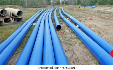 Long blue plastic sewer pipes in the wood. Soon here construction of new houses will begin. Panoramic autumn collage from several outdoors photos