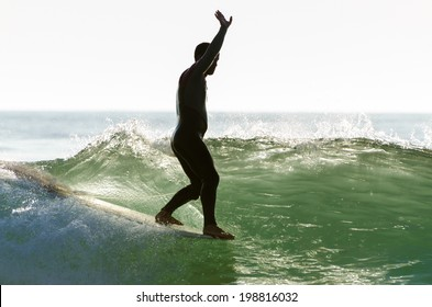 Long boarder surfing the waves at sunset in Portugal.