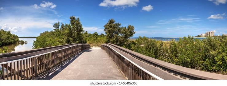 Long Boardwalk leading to the ocean at Lovers Key State Park Beach in Bonita Springs, Florida.