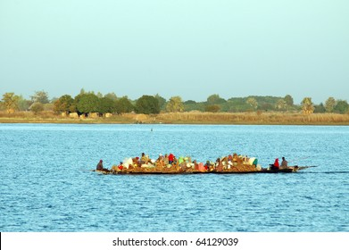 Long boat carrying people and goods across river in West Africa