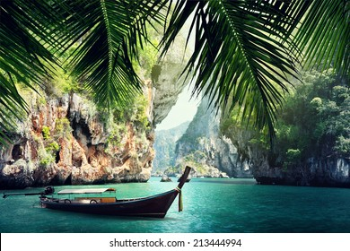 long boat and rocks on beach in Krabi, Thailand